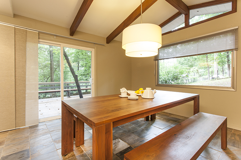 Mid-century modern dining room with vaulted ceiling looking out on spacious deck.